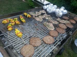 Burger, Mais und Ofenkartoffel auf dem Grill